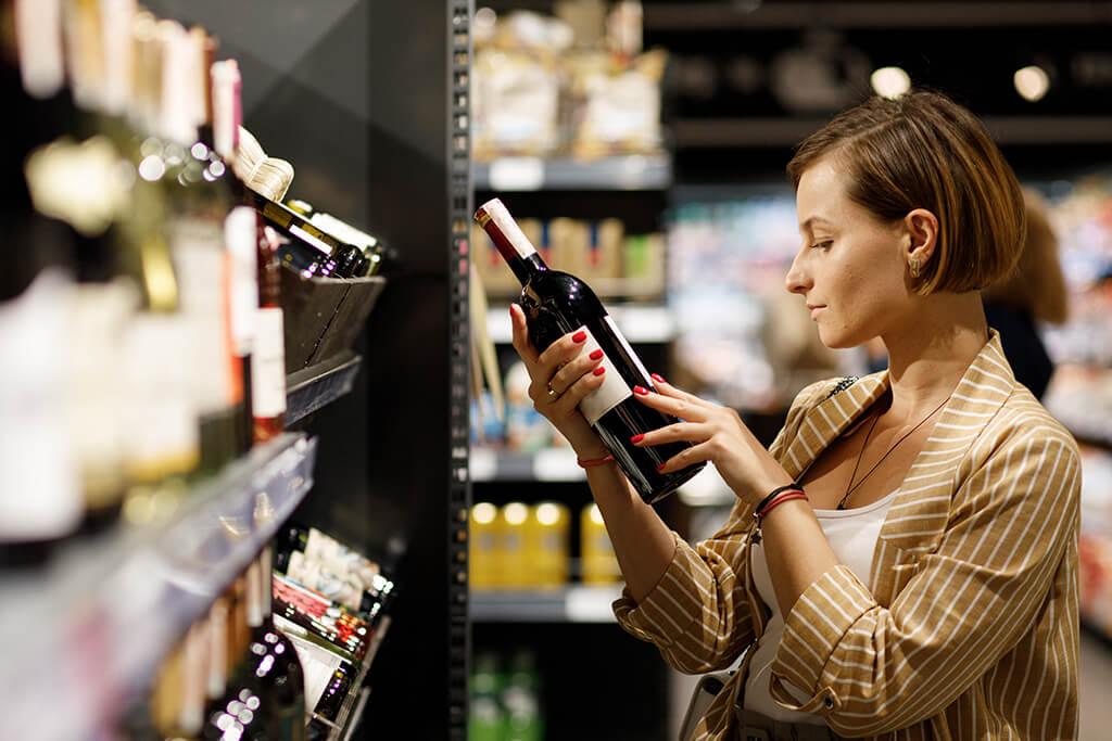 Adega de vinho: Mulher escolhendo um rótulo