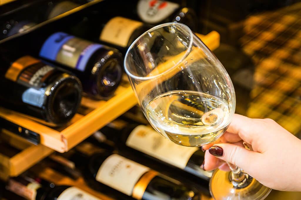Adega de vinho: Mão de uma mulher tomando vinho branco