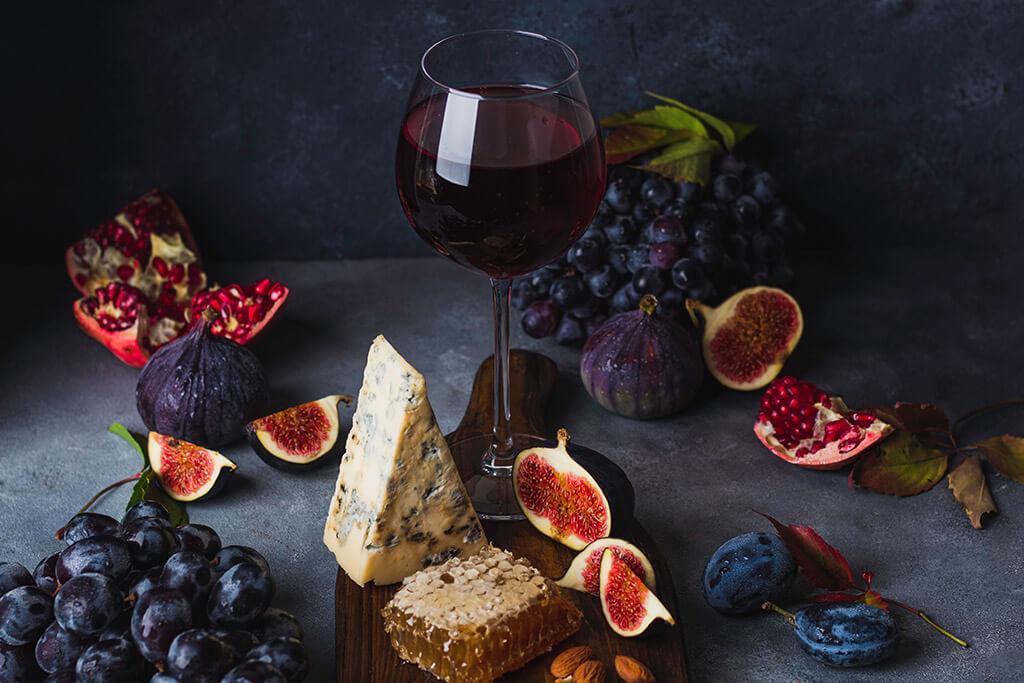 Vinho do Porto: taça de vinho, frutas vermelhas e queijos
